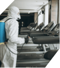 A First Response Cleaning Virus Cleanup Specialist wears a HAZMAT suit while decontaminating a gym