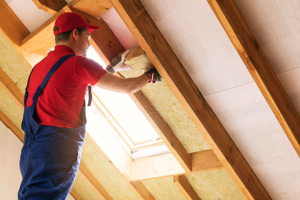 man working on attic insulation roof